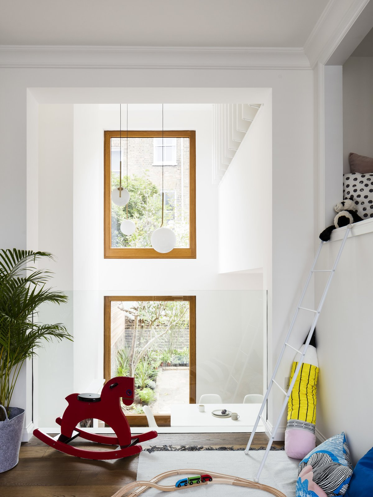 A lofted playroom overlooks the main living space.  A seamless piece of glass provides a discrete barrier. Tagged: Kids Room, Medium Hardwood Floor, Toddler Age, Rockers, Neutral Gender, and Playroom.  Best Photos from A Sleek Renovation in London Ushers Light Into a Family Home