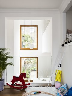 A Sleek Renovation in London Ushers Light Into a Family Home - Photo 4 of 11 - A lofted playroom overlooks the main living space. A seamless piece of glass provides a discrete barrier.