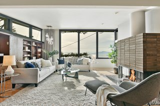 A Bay Area Jewel With Golden Gate Views Wants $1.55M - Photo 2 of 14 - Built-in wood shelving sits below clerestory windows opposite a large brick fireplace with a sculptural chute. Expansive windows provide views of the bay beyond.