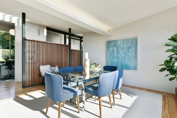 The formal dining room is framed by a wood screen wall which allows light to continually pass inward.