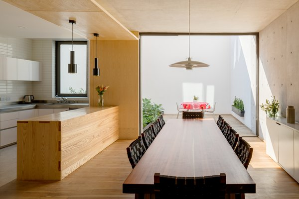 Arrullo Chairs surround an Arrullo Dining Table, both by Oscar Hagerman.  Pendant Light JL341 by Juha Leviska hangs delicately above the wooden table.