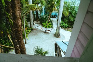 Forget Coworking—These Coliving Spaces Let You Travel the World For $1,800 a Month - Photo 4 of 25 - Roam Miami sandy garden with hammock