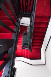 Forget Coworking—These Coliving Spaces Let You Travel the World For $1,800 a Month - Photo 16 of 25 - The Victorian stairwell at Roam London is lush and luxurious, with bold red treads and risers.