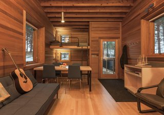 Camp in Style at This Trio of Cedar-Clad Cabins in Minnesota - Photo 6 of 8 - Built-in bunks are decked out with a private window for viewing the outdoors, and an adjustable reading light from Prima Lighting.  A simple pendant hangs above the main space.