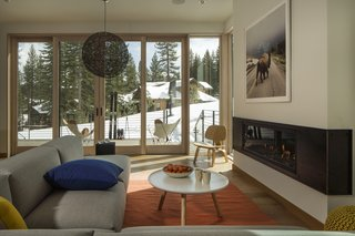 These Contemporary Lake Tahoe Chalets Have Ski-In, Ski-Out Access - Photo 4 of 11 - A Town & Country fireplace anchors the living room, providing a warm space to enjoy the views of the outdoors.