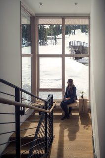 These Contemporary Lake Tahoe Chalets Have Ski-In, Ski-Out Access - Photo 5 of 11 - Adjacent to the staircase, large spans of glazing frame views to the slopes beyond. Wood stair treads and a steel guardrail modernize the circulation space. A George Nelson bench sits below the window, decorated by a Ohio Design Blocky.