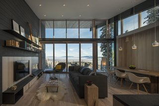 These Contemporary Lake Tahoe Chalets Have Ski-In, Ski-Out Access - Photo 6 of 11 - Built-in storage solutions and floating shelves provide ample storage in the main living space. Homerwood Hickory flooring and exposed structure reach outwards to the views beyond.