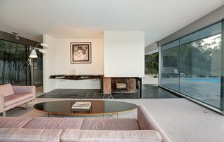Richard Neutra's Stunning Loring House Is Listed For $5.6M - Photo 1 of 10 - Midcentury modern furniture, including a Fat Chance Sofa and Chair, an Eames surfboard coffee table, and a Gino Sarfatti Triennale Lamp by Arteluce, decorate the living room.