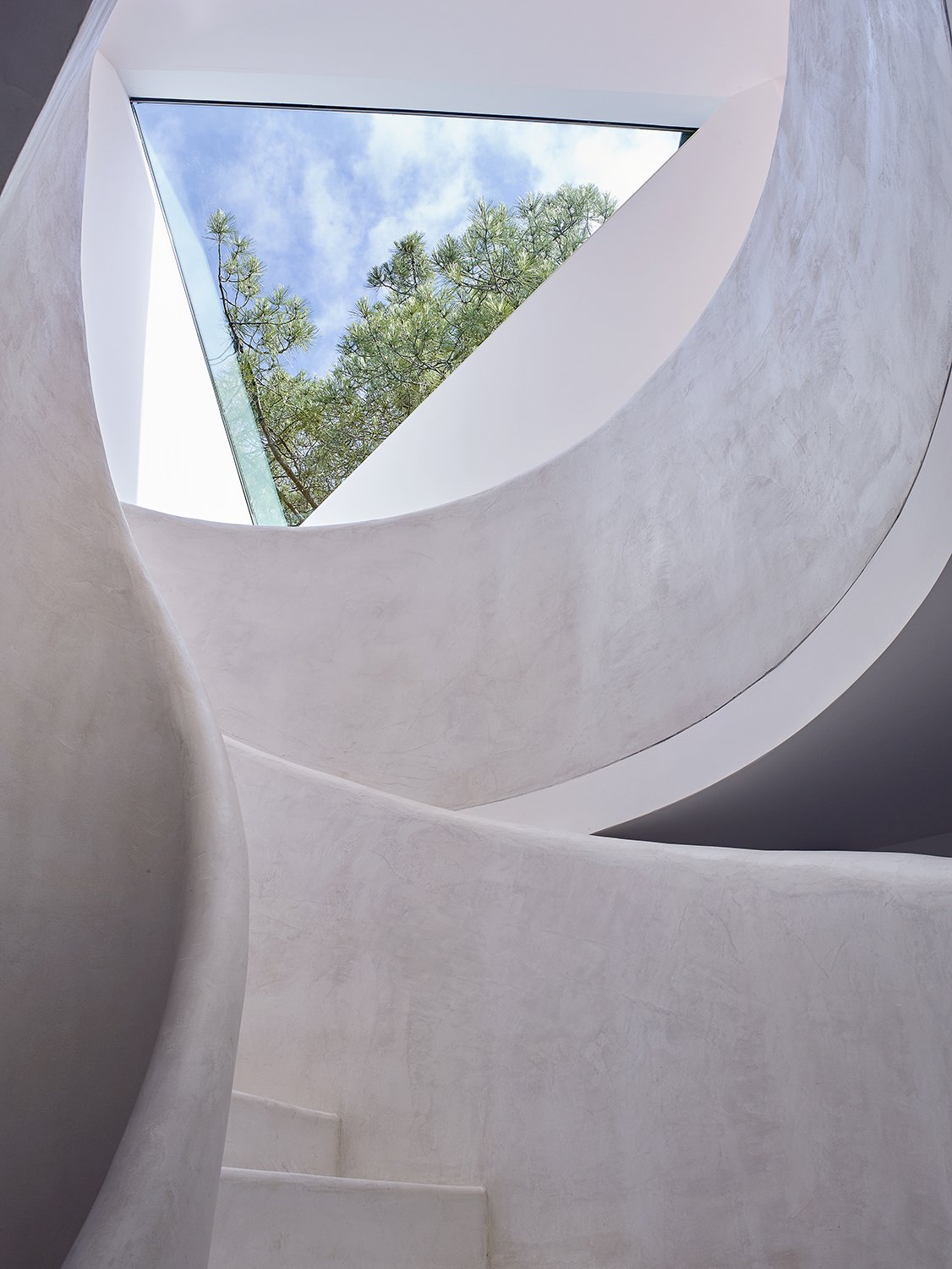 The curvilinear staircase, painted all white, contrasts with the angular forms evident throughout the home.