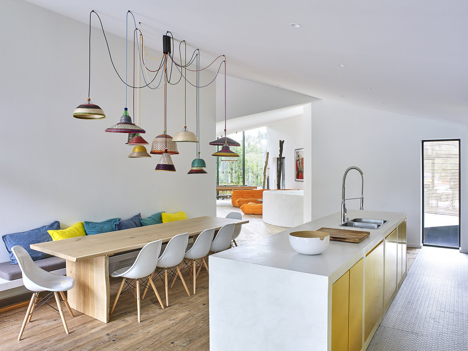 The combined kitchen and dining area is infilled with pops of color.  Metallic gold cabinets and decorative pendants by Alvaro Catalan de Ocon accent the open space.