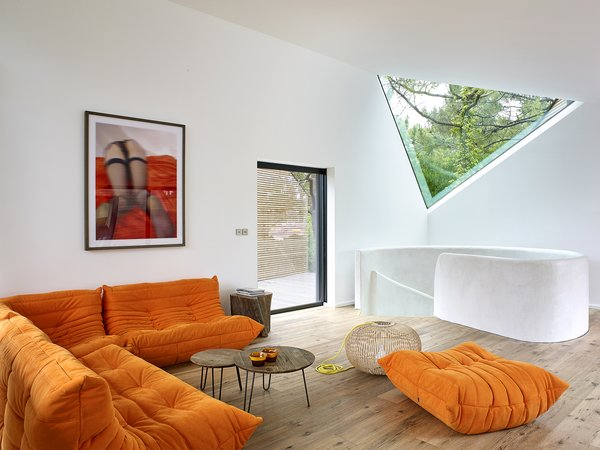 An orange Ligne Roset Sofa provides a comfortable space for rest and relaxation.  A triangular window provides a picture of the tree canopy beyond, while drawing in natural light.