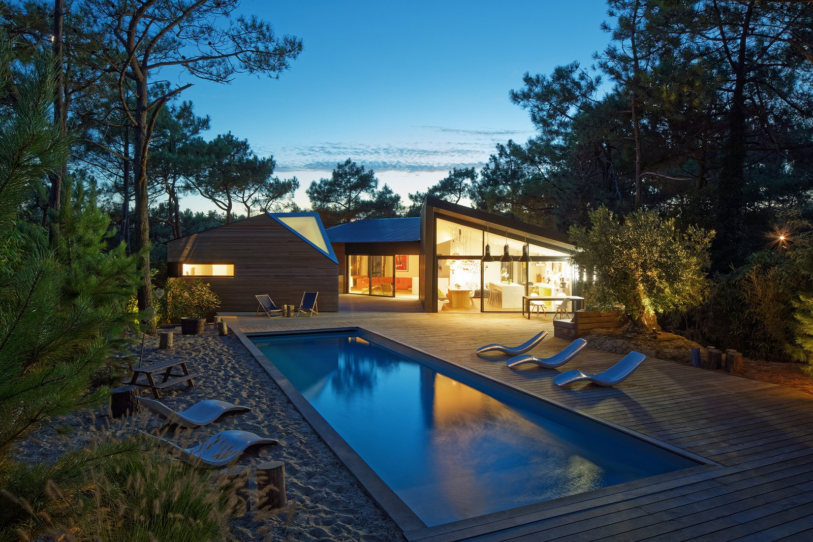 At sunset, the holiday home glows like a shining lantern set within the forest.