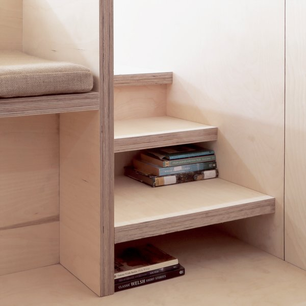 Stairs leading up to the platform bed double as storage for books.