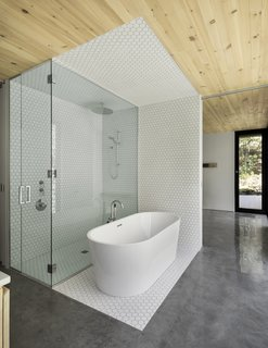 This Wood-Clad Home Is Built Into a Serene Mountain Slope - Photo 11 of 16 - White, hexagon tiles frame the shower and tub in the master bath. On the opposite wall, full-height glazing connects the users directly with the landscape.