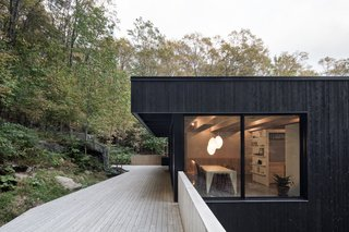 This Wood-Clad Home Is Built Into a Serene Mountain Slope - Photo 4 of 16 - The dark-stained exterior cladding stands in contrast to the light wood decking and warm interiors.