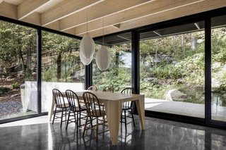 This Wood-Clad Home Is Built Into a Serene Mountain Slope - Photo 9 of 16 - A custom-designed wooden dining table is surrounded by chairs acquired at Saint-Michel Flea Market in Montreal.  IKEA pendant lamps decorate the space.