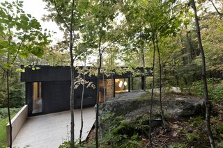 This Wood-Clad Home Is Built Into a Serene Mountain Slope - Photo 14 of 16 - The home appears as if it is carved into the mountainside, serving as one with the trees and rock formations.