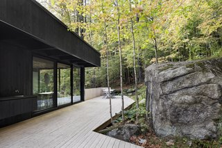 This Wood-Clad Home Is Built Into a Serene Mountain Slope - Photo 5 of 16 - The exterior deck gracefully meanders its way around the rock formations.