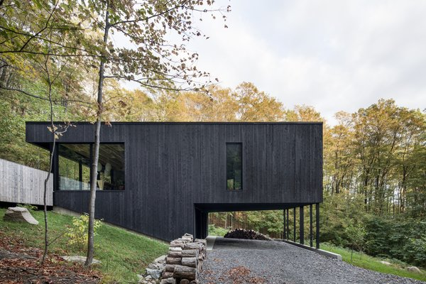 This Wood-Clad Home Is Built Into a Serene Mountain Slope - Photo 1 of 16 - Supported on thin columns, the main volume hovers above the graveled entry, reaching out into the surroundings.