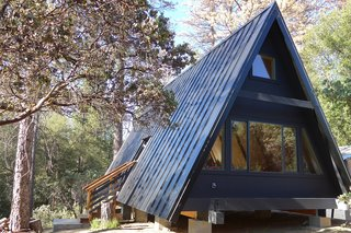 11 Alluring A-Frame Homes You Can Rent Right Now - Photo 10 of 11 - This modern A-frame cabin near Yosemite can accommodate three guests. The A-Frame shape fills the cabin with natural light, and a dark clad exterior contrasts with the warm, honeyed hues of the interior.