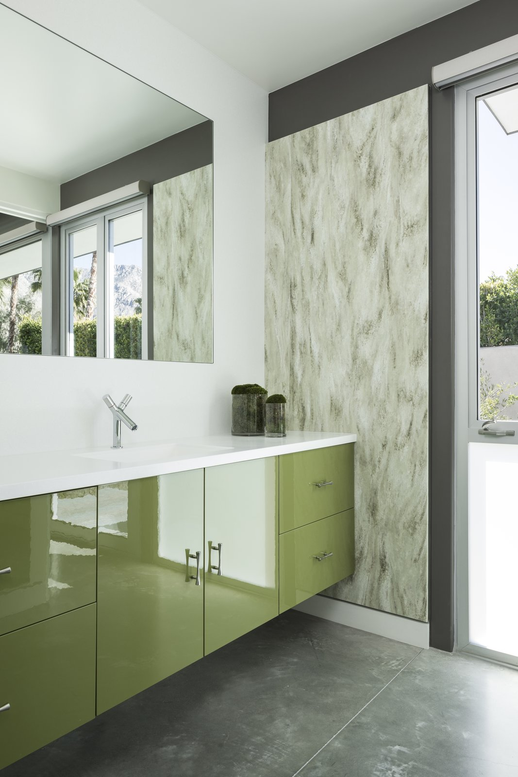 Glossy green cabinets, textured wall coverings, and polished concrete floors, in dessert hues, decorate one of the guest baths.