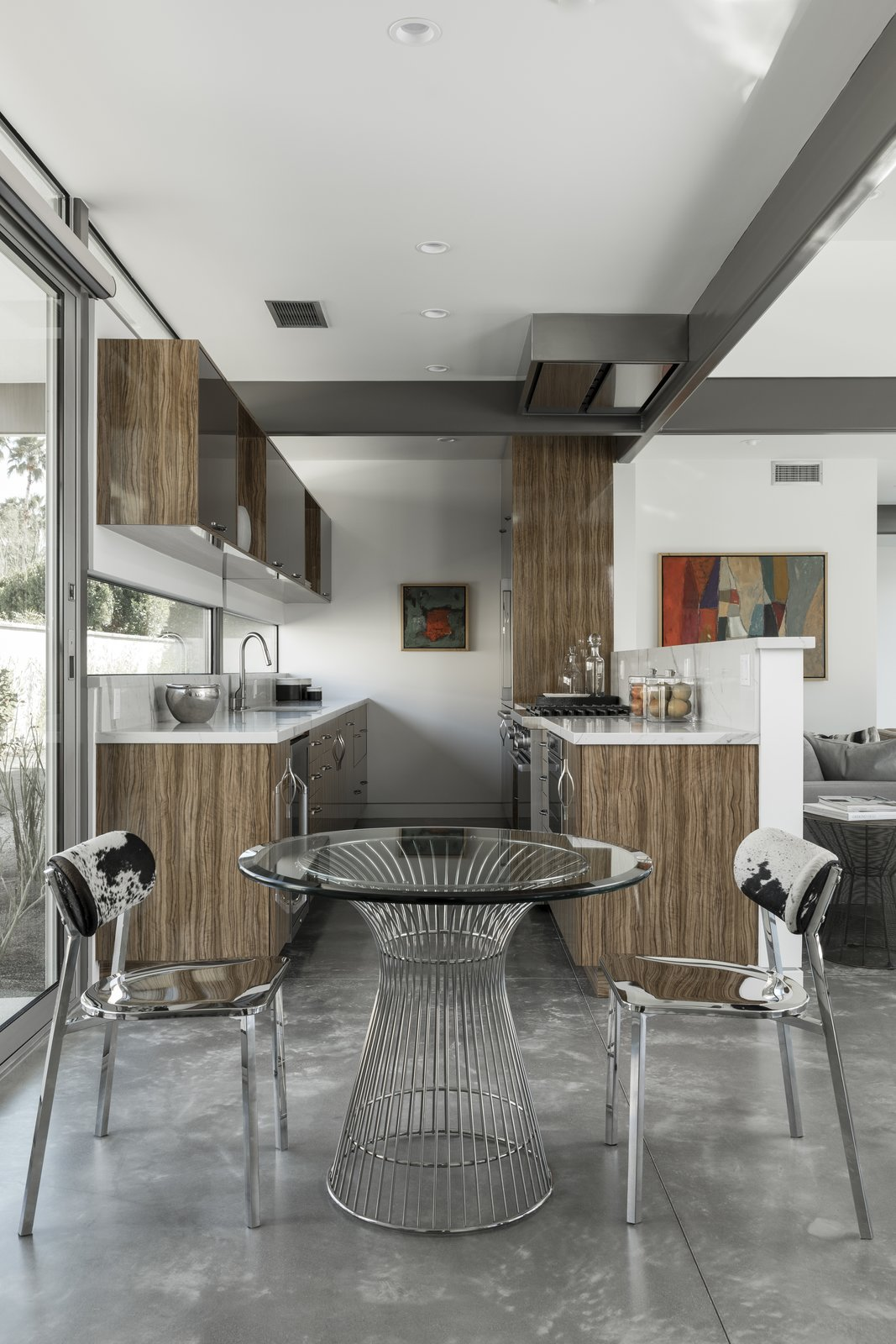 A contemporary kitchen with wood cabinetry provides an open, fluid cooking space.  The cooktop hood nestles perfectly against the structural framing.