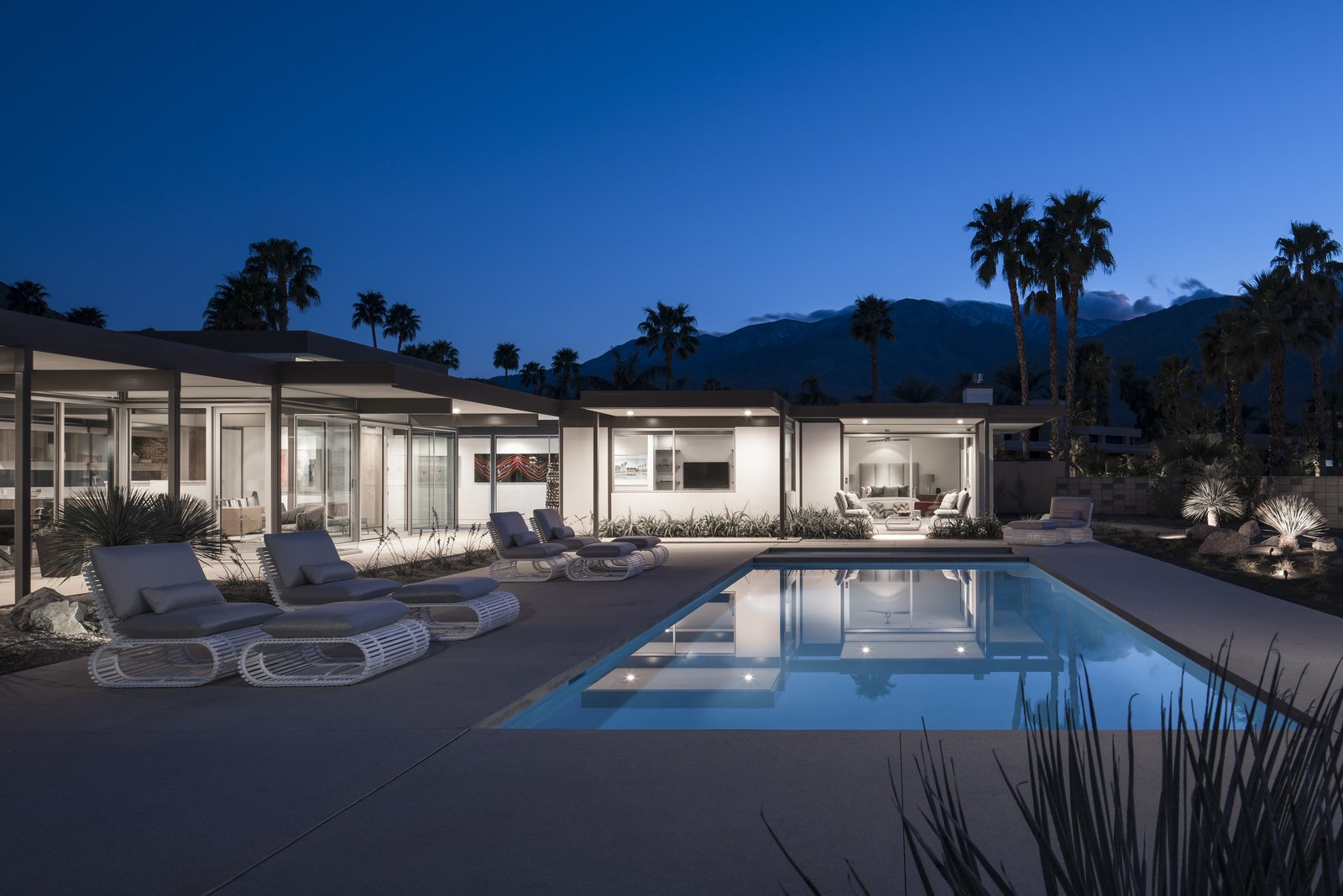 At dusk, the lightly colored home glows like a lantern in the dessert sky.