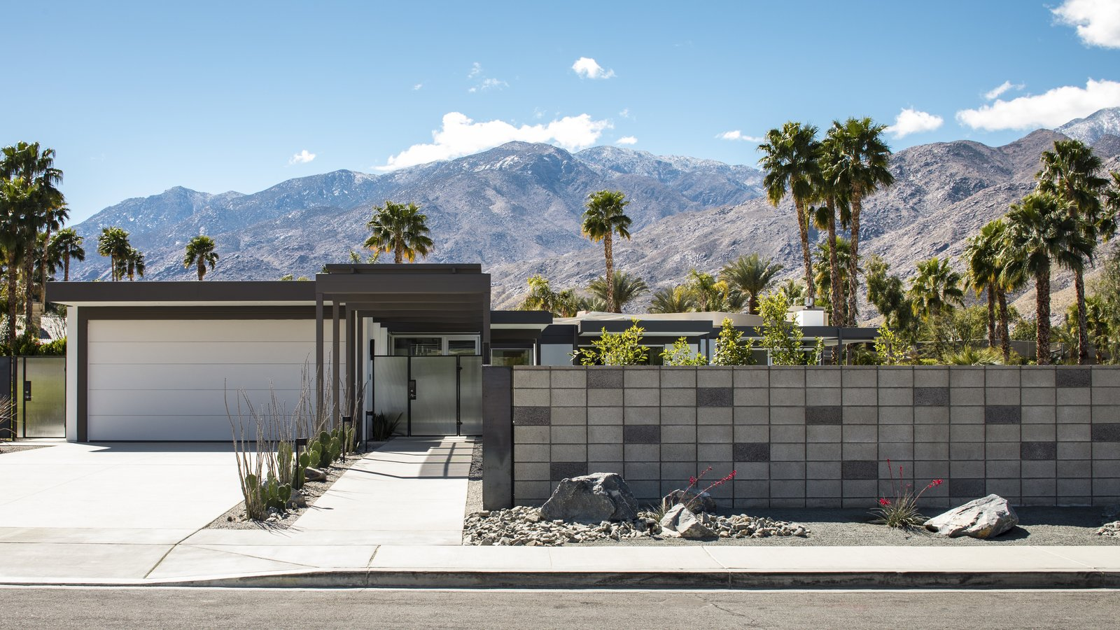 A steel framed canopy leads directly to the front entry of the dwelling.  A concrete block fence provides privacy from the surrounding neighborhood. Drought tolerant landscaping dots the landscape.