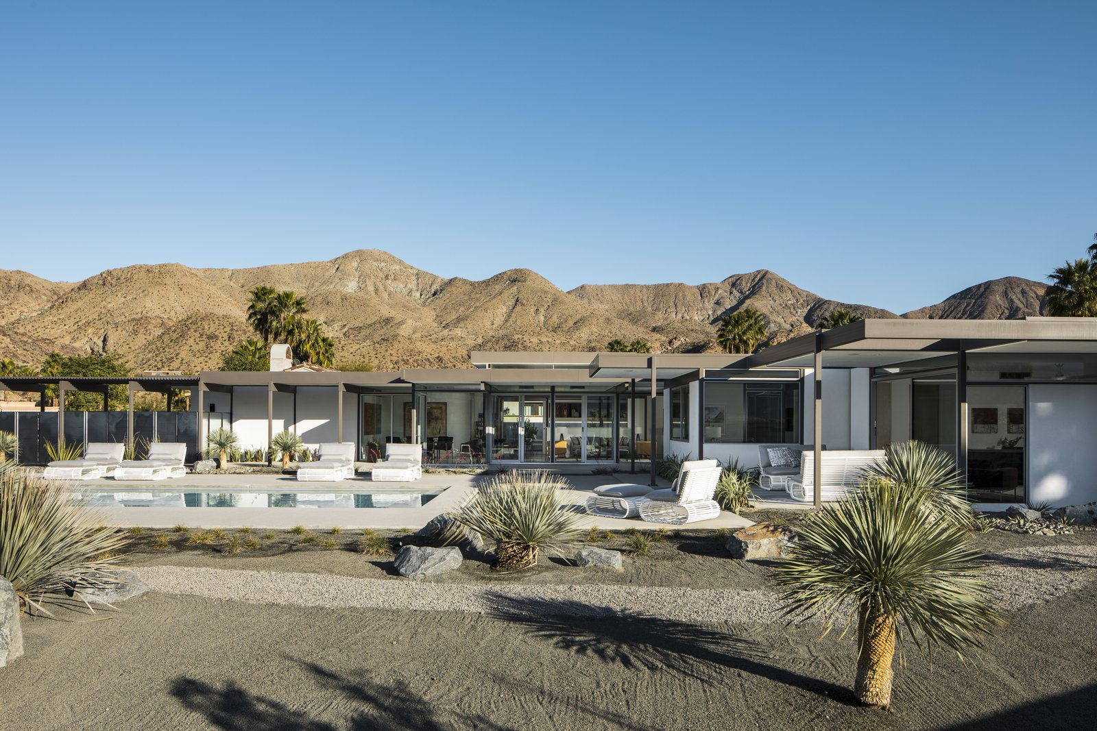 Mountainous terrain surrounds the modern, desert home.  Horizontal roof planes extend outward, connected the home to the dessert land.
