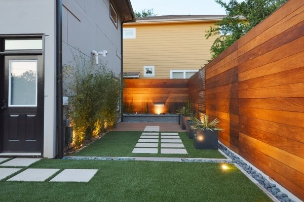 Modern home with outdoor, back yard, hardscapes, grass, small patio, porch, deck, wood patio, porch, deck, horizontal fence, wood fence, and landscape lighting. Symmetry  Photo 2 of White House
