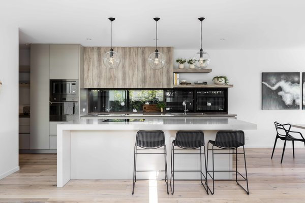 Modern home with kitchen, stone counter, wood cabinet, light hardwood floor, ceiling lighting, pendant lighting, range hood, and wall oven. Photo 3 of The Rose Bay House