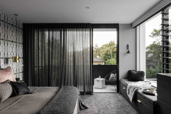 Modern home with bedroom, bed, pendant lighting, bench, storage, chair, and carpet floor. Photo 7 of The Rose Bay House