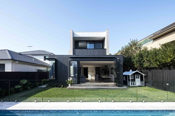 Modern home with outdoor, grass, shrubs, back yard, small patio, porch, deck, and swimming pool. Photo 9 of The Rose Bay House