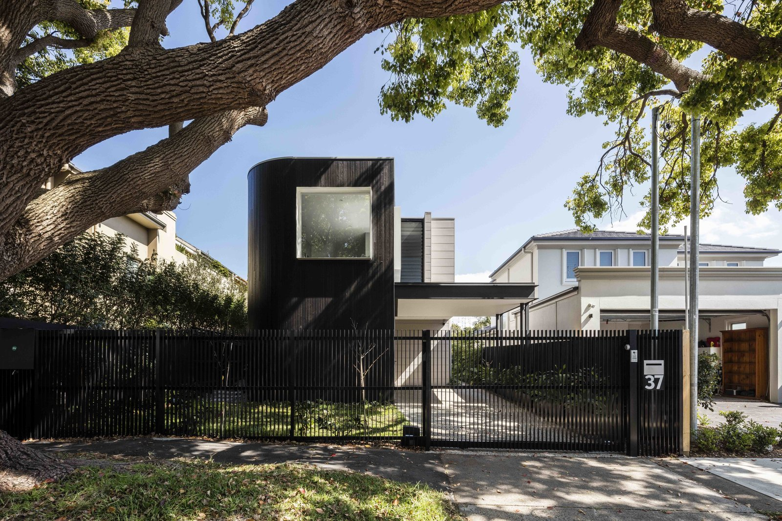 Tagged: Outdoor, Front Yard, Trees, Grass, Vertical Fences, Wall, and Metal Fences, Wall.  The Rose Bay House by Prebuilt