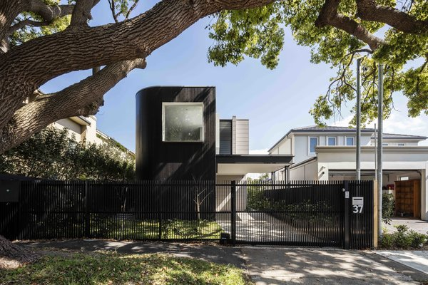 Modern home with outdoor, front yard, trees, grass, vertical fence, and metal fence. Photo 8 of The Rose Bay House