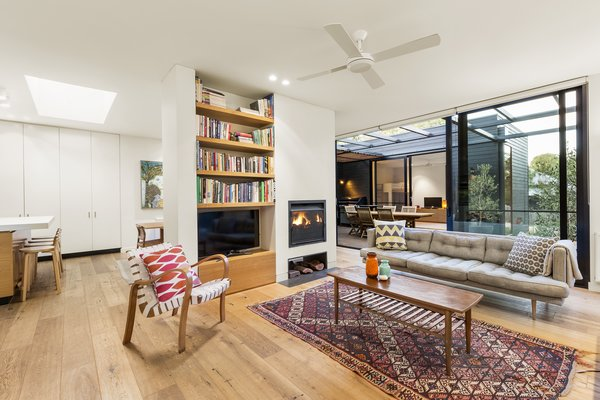 Modern home with living room, coffee tables, sofa, chair, two-sided fireplace, and medium hardwood floor. Photo 5 of The Merricks Beach House