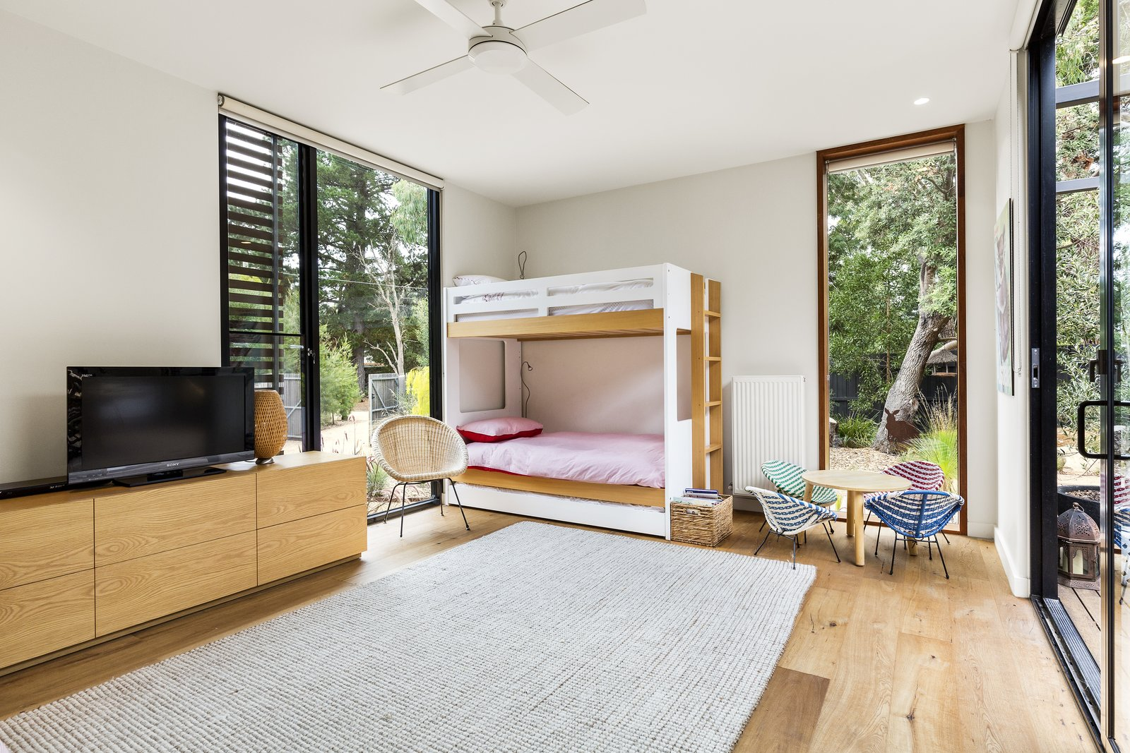 Tagged: Kids Room, Bedroom, Bunks, Storage, Chair, Medium Hardwood Floor, Neutral Gender, and Pre-Teen Age.  The Merricks Beach House by Prebuilt