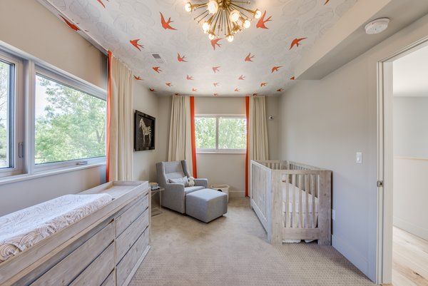 Modern home with bedroom, ceiling lighting, rockers, bed, dresser, and carpet floor. Nursery Photo  of The Ryan House