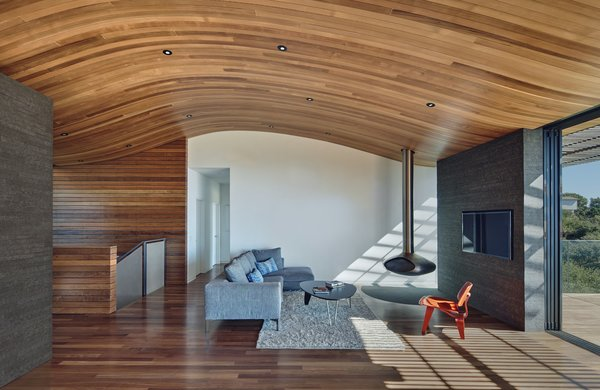 Modern home with living room, chair, ceiling lighting, recessed lighting, medium hardwood floor, and corner fireplace. Living area Photo 5 of Skyline House