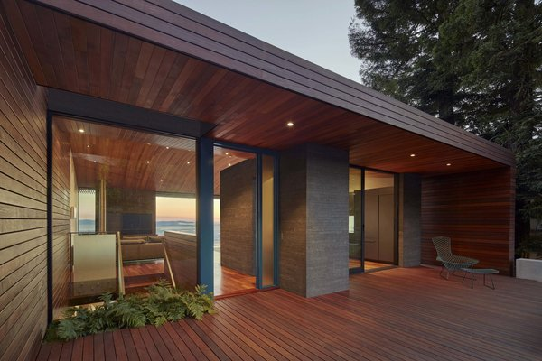 Modern home with outdoor, front yard, shrubs, small patio, porch, deck, and wood patio, porch, deck. Entry at dusk Photo 10 of Skyline House