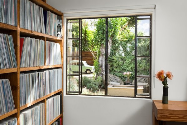 Bedroom with built-in wood shelves for records.  Steel window with view to rear yard landscape and firepit