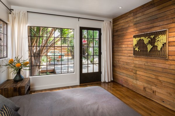 Modern home with night stands, medium hardwood floor, recessed lighting, bed, swing door type, exterior, wood, windows, picture window type, casement window type, and metal. Bedroom with steel windows to view and access rear yard deck.  Art by Chris McCullough Photo 12 of Boise Residence