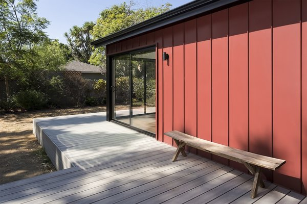 Modern home with back yard, shrubs, trees, large patio, porch, deck, wood patio, porch, deck, decking patio, porch, deck, doors, metal, sliding door type, and exterior. Detail of red standing seam metal siding with bench at raised deck and corner sliding door unit Photo 3 of Allaseba Residence