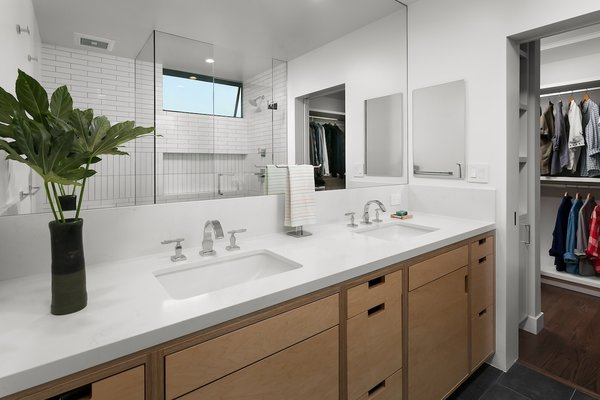 Modern home with engineered quartz counter, undermount sink, enclosed shower, porcelain tile floor, recessed lighting, subway tile wall, windows, two piece toilet, awning window type, and metal. Bathroom off walk-in closet Photo 12 of Allaseba Residence