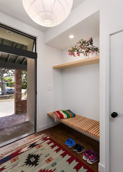 Modern home with medium hardwood floor, wood, exterior, swing door type, awning window type, metal, shelves storage type, closet storage type, and kids room. Entry with built-in bench and shelf Photo 14 of Allaseba Residence