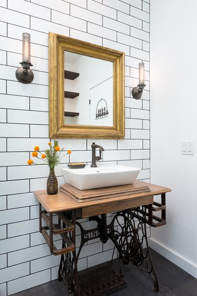 Modern home with bath room, wood counter, porcelain tile floor, vessel sink, corner shower, wall lighting, subway tile wall, and two piece toilet. Reclaimed sewing machine vanity at bathroom Photo 11 of Woodland Hills Residence