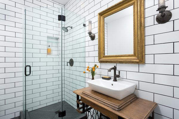 Modern home with bath room, porcelain tile floor, wood counter, corner shower, vessel sink, wall lighting, subway tile wall, and two piece toilet. Bathroom with corner shower and reclaimed sewing machine vanity Photo 10 of Woodland Hills Residence