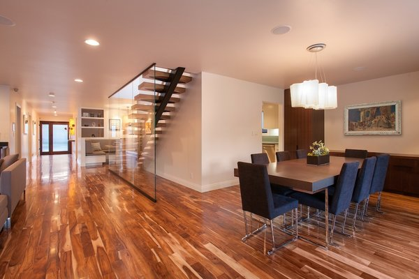 Modern home with chair, pendant lighting, table, bar, recessed lighting, medium hardwood floor, metal, exterior, swing door type, staircase, wood tread, and glass railing. Dining Room and staircase with Entry beyond Photo 9 of Bowling Green Residence