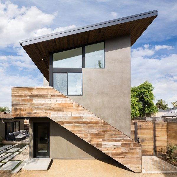 Modern home with back yard, side yard, desert, trees, hardscapes, walkways, wood patio, porch, deck, small patio, porch, deck, concrete patio, porch, deck, decking patio, porch, deck, decomposed granite patio, porch, deck, horizontal fence, hanging lighting, pavers patio, porch, deck, wood fence, sliding window type, picture window type, metal, wood railing, and wood tread. Access to the art studio is created by an exterior staircase clad in reclaimed wood Photo 2 of Mar Vista Art Studio