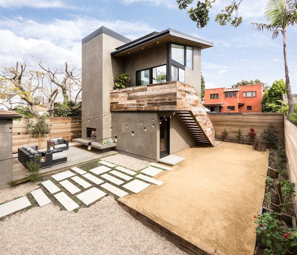 Modern home with side yard, desert, trees, back yard, hardscapes, gardens, walkways, small patio, porch, deck, wood patio, porch, deck, concrete patio, porch, deck, decking patio, porch, deck, pavers patio, porch, deck, decomposed granite patio, porch, deck, horizontal fence, wood fence, hanging lighting, exterior, metal, sliding door type, and picture window type. Located in the corner of the lot, the 2-story art studio is connected to the existing main house via a raised deck with outdoor fireplace and a meandering hardscape path  Photo  of Mar Vista Art Studio